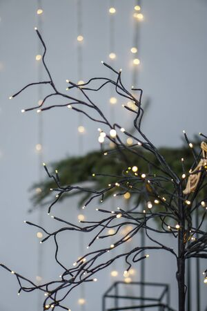Beautiful yellow garlands in an interesting composition on the background of a Christmas tree. New Year theme for design