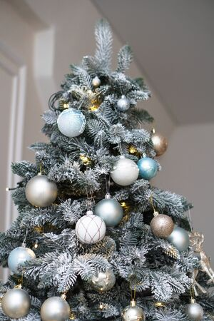 Christmas tree decorated with toys and a garland. New year background for your design. Seasonal holidays in winter