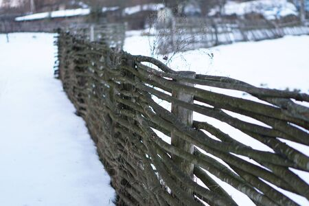 Winter landscape outside the city in the forest. Snowy fence in December. Christmas and New Year picture. Banco de Imagens