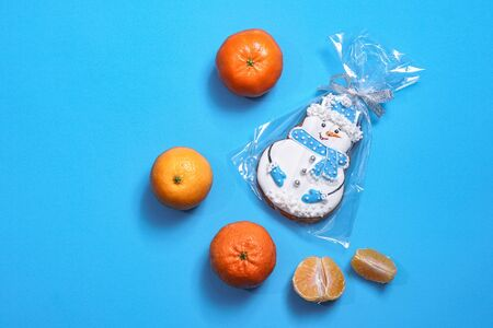 Beautiful round gingerbread cookie in the shape of a snowman on a blue background. Winter Christmas and New Year theme