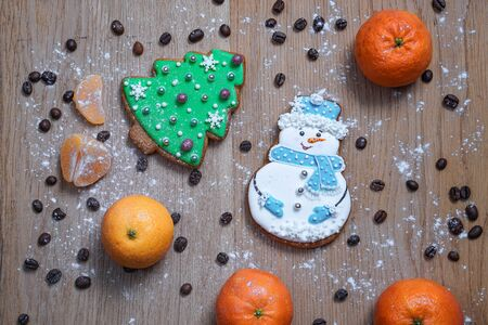 Beautiful gingerbread cookie in the form of a snowman and a Christmas tree on a background of a wooden texture with coffee grains. Winter christmas theme 写真素材