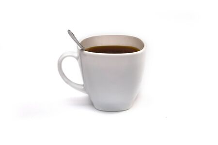 White cup of coffee with a spoon on an isolated background. Black cappuccino drink in a bowl