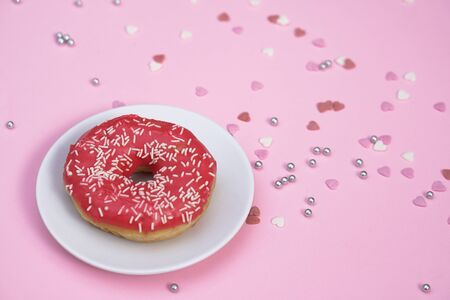 Beautiful juicy donut with a sweet cream. Cupcake on a pink background for kitchen design. 写真素材