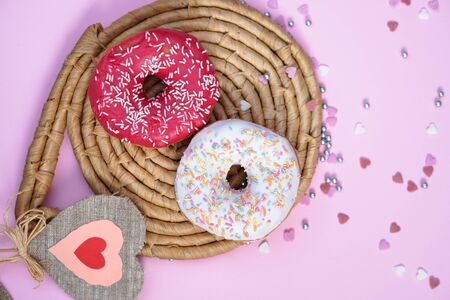 Beautiful juicy donuts with sweet in plates on a decorative tray. Cupcake on a pink background with colorful hearts for kitchen design