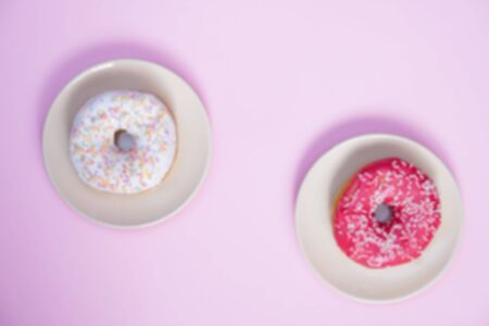 Beautiful juicy donut with a sweet cream. Cupcake on a pink background for kitchen design. Banco de Imagens