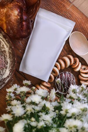 Template of paper ecological bag for storing coffee, tea on a wooden kitchen table with sweets. making donuts and croissants for the holiday Banco de Imagens