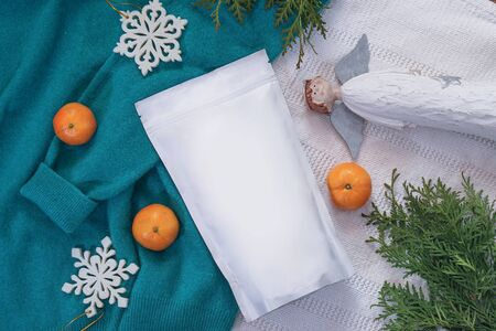 Template of ecological paper bag for storing coffee, tea on the background of decorations and adornments. Vacuum packaging for christmas and new year present