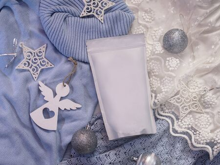 Template of ecological paper bag for storing coffee, tea on the background of decorations and adornments for the winter holiday. Vacuum packaging for christmas and new year present