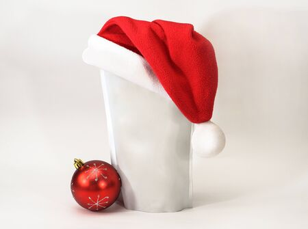 Template of paper ecological bag for storing coffee, tea on an isolated white background in a red hat and a round toy. Vacuum packaging for christmas and new year present