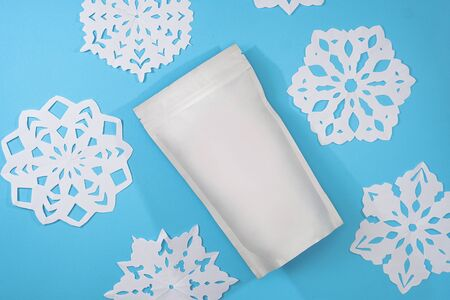 Template of paper ecological bag for storing coffee, tea on an isolated blue background with handmade snowflakes. Vacuum packaging for christmas and new year present