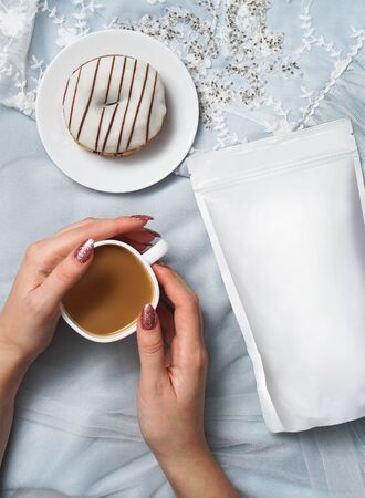 Template of paper ecological bag for storing coffee, tea on the background of a female dress and hands with cappuccino. Vacuum packaging for christmas and new year present Banco de Imagens
