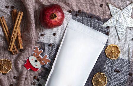 Template of ecological paper bag for storing coffee, tea on the background of dried fruits and decorations. Vacuum packaging for christmas and new year present