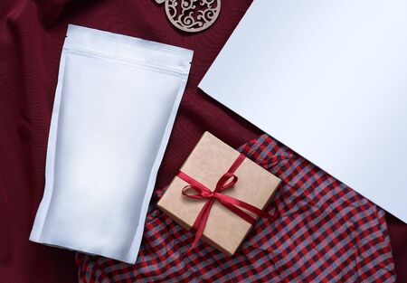 Template of paper ecological bag for storing coffee, tea on the background of a gift in a box. Vacuum packaging for christmas and new year present