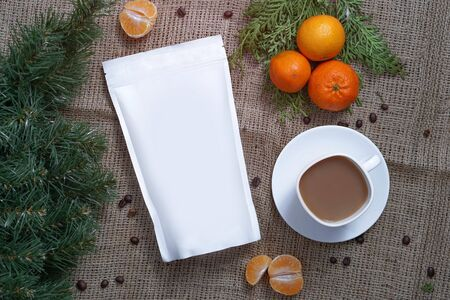 Template of paper ecological bag for storing coffee, tea on a background of texture and a cup of cappuccino with tangerines. Vacuum packaging for christmas and new year present Banco de Imagens