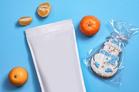 Template of paper ecological bag for storing coffee, tea with snowman-shaped cookies and tangerines. Vacuum packaging for christmas and new year present