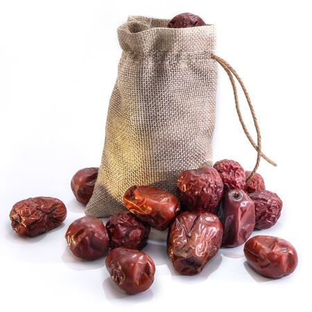 Large dates on a white isolated background. Plum and dried fruit food for your website design. kitchen theme Archivio Fotografico