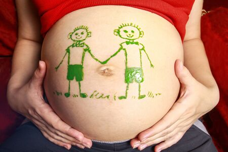 Pregnant with a big belly and a pattern on it. Images of two twin boys. Parents are waiting for twins .Stock photo