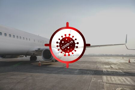 Sign warns of a coronavirus in the background of an airplane. In the sight of a new threat, a global pandemic and quarantine. COVID-19 prevents planes from taking off from an airport