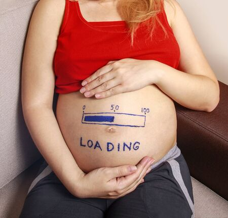 Pregnant with a big belly and a pattern on it. Fifty percent load. Half of the pregnancy has already been completed. Stock photo