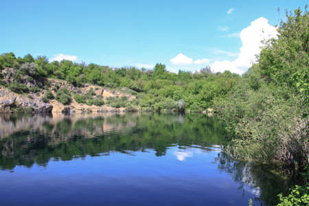 Beautiful river in the highlands in summer. Lake in an ecologically clean park reserve on a background of hills. A pretty landscape in the spring. Stock photo for design