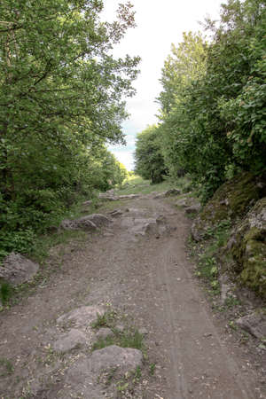 Nice mountain road with a beautiful view. A rock on the side of a dirt path. Stock landscape for design