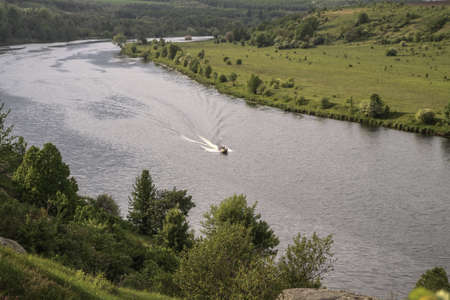 Top view of the river with a fast-moving motorboat with tourists in a nature reserve. Fishermen sail on the ship for the catch. Beautiful pretty landscape. Stock photo
