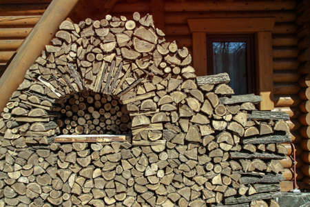 Addition of firewood for the winter. Logging in the village for tourists. Wood cut into small pieces for a fireplace or a bonfire. Stock photo