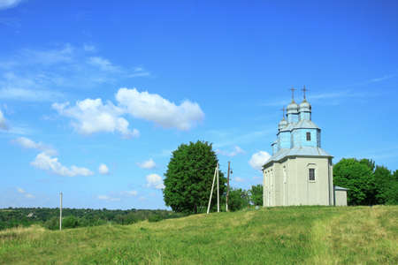 Church on a hill on the outskirts of the village. Christian temple landscape in Russia. Stock photo background