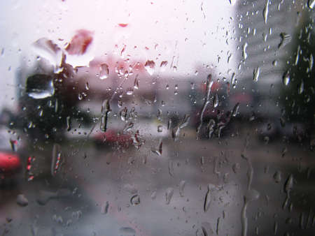 Drops on glass overlooking the street. Car window and the road behind it. Urban theme stock photo for design