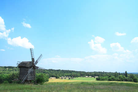 Landscape on a summer day against the backdrop of a beautiful ancient village with beautiful houses and mills. Stock photo for design Фото со стока - 158267186
