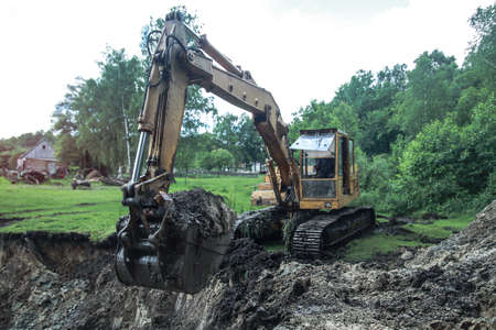 An excavator digs a large trench for building a house. A tractor digs a large lake that is already gaining water. Stock background for design Фото со стока - 157857251
