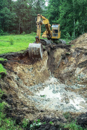 An excavator digs a large trench for building a house. A tractor digs a large lake that is already gaining water. Stock background for design Фото со стока
