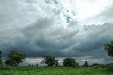 Thunderous epic clouds in a field near the old garden. Stock photo background with heaven.