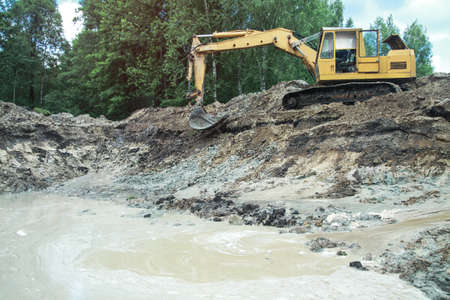 An excavator digs a large trench for building a house. A tractor digs a large lake that is already gaining water. Stock background for design Фото со стока - 157857284