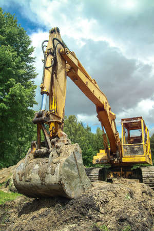 An excavator digs a large trench for building a house. A tractor digs a large lake that is already gaining water. Stock background for design Banco de Imagens