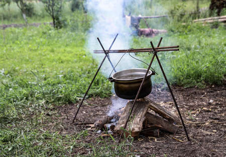 Bonfire and bowler on a background of nature. Summer camping in the park or outdoors