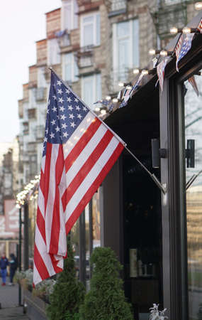 American flag on a building near the road against the background of the city. USA Symbol of power for Independence Day. Urban Temma Nu York. Stock photo