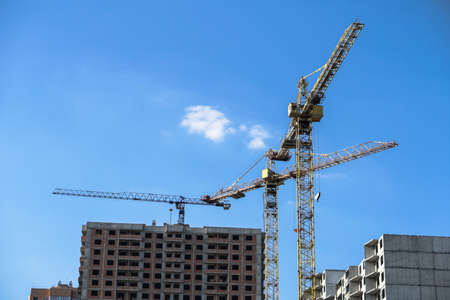 Multi-stage construction during the construction process with a yellow crane. Industrial background for design.