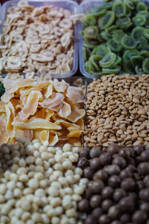 Rack on the market with dried fruits and nuts and Turkish sweets. Vegetarian food mix. Stock photo background for business