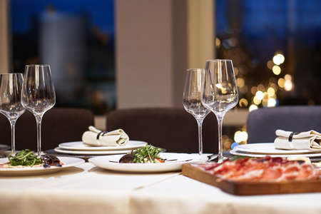 Nicely served New Year's table in the restaurant. Christmas night in a cafe or at home. Stock photo for design