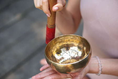 Meditation with vibrations from the bowl in the lotus position. Nature yoga theme hands and bronze utensils. soul music on an instrument