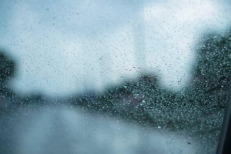 Car glass in drops from rain. Autumn summer rain through the car window. Photo background Фото со стока