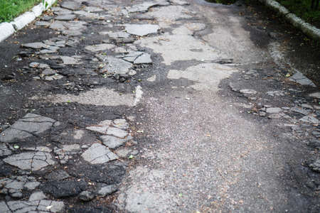 Destroyed road in poor condition requiring repair. Holes in the asphalt are filled with water and puddles. Stock photo background