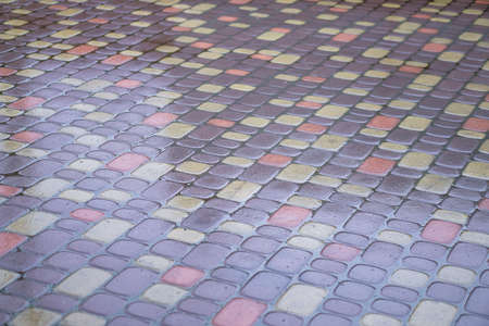 Multi-colored paving stones in the water. The texture of stones in the rain. Photo background