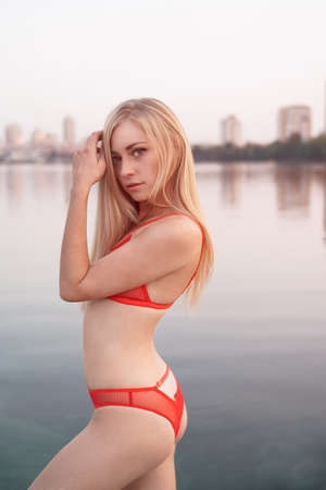 Beautiful blonde girl in a swimsuit near a pond against the background of the city. Sexy girl in lingerie.
