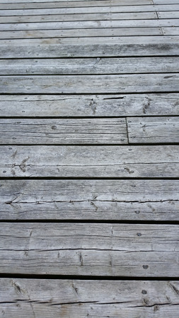 silvery: Silvery worn wood planks run horizonally as a background with character. Top planks recede into distance.