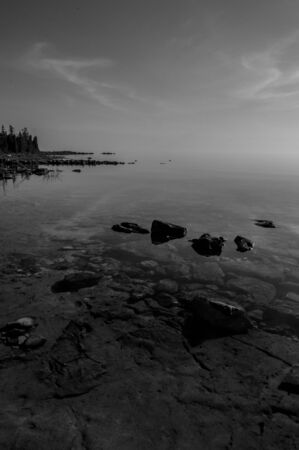 Dead calm afternoon image of clear lake huron water and limestone rocks along shoreline.  Clouds reflecting in a zign zag. bw