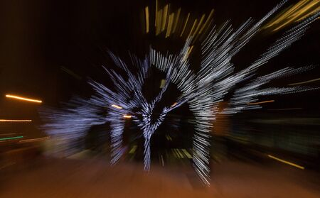disturbing: Four Christmas holiday light covered trees are blurred into a dynamic, bright night time image.  Office building lights and streetlights are also intentionally blurred in this slightly distubing, fast-moving image.