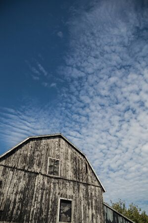 An abstract wide angle of a traditional old ontario gambrel roof barn, that was black and is weathered and the boards lit up by sunshine. Sky is a deep blue with interesting cloudscapes of cirrus clouds as a background.