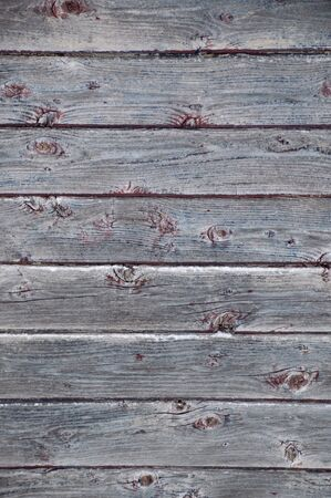 outbuilding: Background portrait oriented image of 8 grunge peeled silver grey weathered barn boards with remannts of red and blue paint.  Small ledges of snow on this outdoor image. Stock Photo